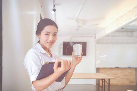 Foto de Retrato de la sonriente mujer de negocios bastante joven en el lugar de trabajo, Calcular el costo de envío de un paquete pequeño, Las pequeñas empresas de las preocupaciones para las compras en línea - Imagen libre de derechos