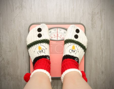 girl standing on floor scales in Christmas socks