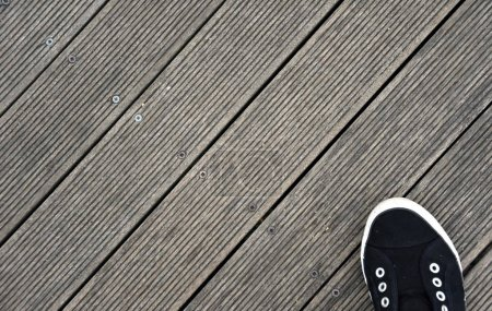Black and white Shoes stand on old wooden pier floor