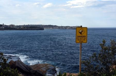"""Sign at the cliff's edge shows """"Danger."""