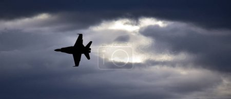 Silhouette of F18 Hornet fighter aircraft in flight.