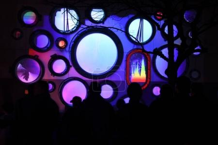"""People watching and taking photos at the """"Portholes"""" art"""