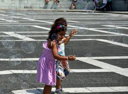 Kids catching and having fun with soap bubbles