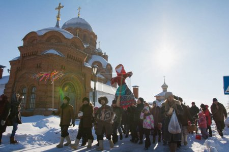 Kazan, Russia - 28 february 2017 - Sviyazhsk Island : The pancake week - Russian ethnical carnival Maslenitsa, Shrovetide, the crowd carries the effigy of winter to burn - in front of church