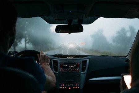 Man driving a car in fog