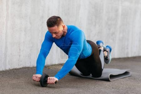 Muscular bodybuilder guy with roller