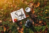 Cup of coffee and book on autumn grass