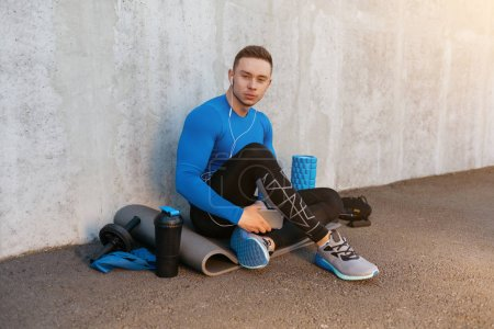 Young sports man listening music