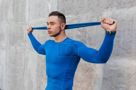 Muscular bodybuilder guy with rubber band