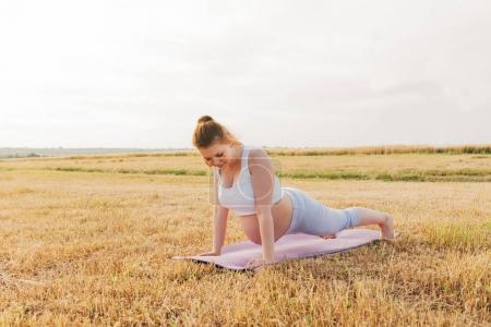 Pregnant woman performing yoga outdoor