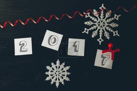 2017 numbers decorated with serpentine and snowflakes and bow on black wooden background