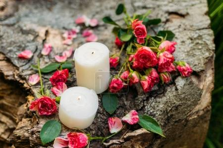 White candles with roses and green leaves on brown wooden background. Romantic atmosphere outdoors
