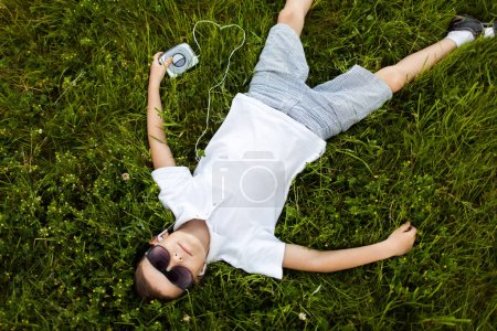 Little boy in sunglasses lying on ground and listening to music in earphones