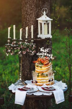 Served table with candle holder and beautiful wedding cake, placed outdoors on lawn