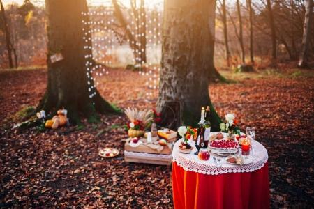 Romantic dinner for two. Desk, flowers, candles, glasses and wine. Evening light. Very romantic photo at sunset