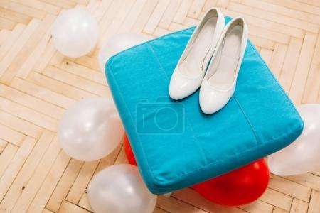 Wedding female white shoes lying on blue stand. Beside scattered white and red balloons. Wedding concept