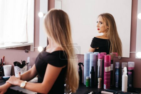 Beautiful woman in black dress with professional make up sitting on chair in beauty salon
