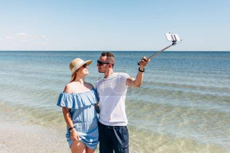 Photo pour Voyage jeune couple prenant selfie photo avec selfie bâton et smartphone, sur la plage de sable près de la mer - image libre de droit