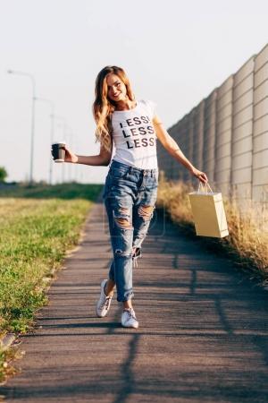 Photo pour Jeune belle femme en vêtements décontractés souriant et sautant sur la route par une journée ensoleillée - image libre de droit