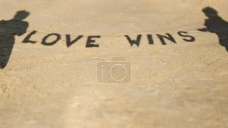 Shadow of two people hanging signboard with text Love wins
