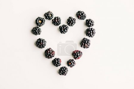 Top view shot of blueberries placed in a shape of heart on white table