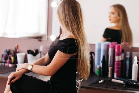 Photo pour Belle femme en robe noire avec maquillage professionnel assis sur une chaise dans un salon de beauté - image libre de droit