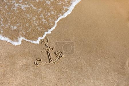 Anchor drawn on the beach sand. Summer holidays background