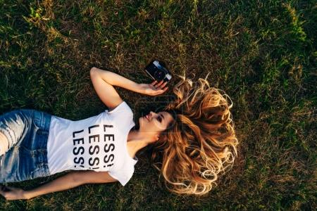 woman lying on lawn with camera