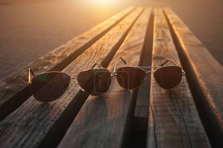 Photo for Closeup shot of two pairs of sunglasses on wooden surface, backlit by setting sun - Royalty Free Image