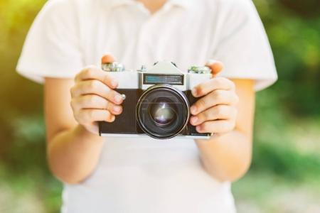 Little kid boy with retro photo camera standing in the green park on s sunny day. Outdoors. Young photographer. Close up