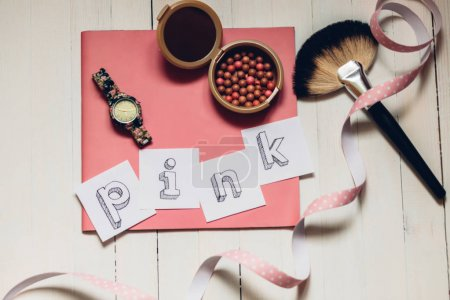 "Word ""pink"" on pink journal with powder, brush and watch. On white wooden table. Girls mood"