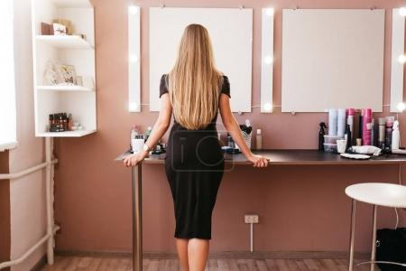 Beautiful woman in black dress with professional make up standing in beauty salon