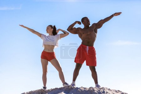 athletic couple flexing muscles