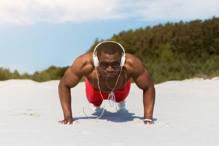 man doing push ups on beach