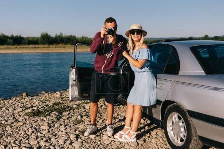 Photo pour Couple voyageur heureux debout près du coffre ouvert de la voiture et regarder le lever du soleil - image libre de droit