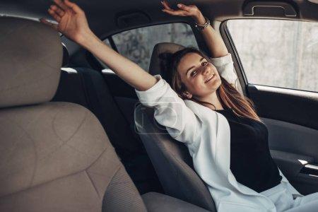 Photo pour Fille élégante de conducteur de mode dans le costume blanc s'asseyant dans la voiture - image libre de droit