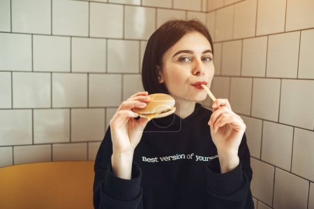 """Photo for Beautiful Brunette Girl in Black Pullover with Text ''Best Version of Yourself"""" Holding a Tasty Burger and French Fries - Royalty Free Image"""