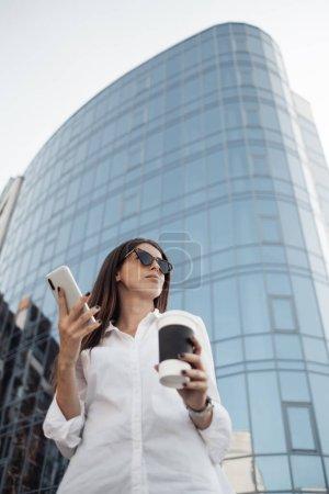 Photo pour Portrait d'une fille à la mode vêtue de jeans et de chemise blanche buvant du café et utilisant son téléphone intelligent, une femme d'affaires et une femme d'affaires Concept énergétique - image libre de droit