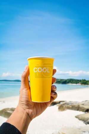 Female hand holding yellow cup with cool word  sea and blue sky background ,concept time to vacation
