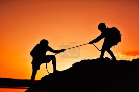 Foto de Silueta de niña ayudando a éxito de trabajo en equipo hombre en alta montaña durante la puesta de sol cielo - Imagen libre de derechos