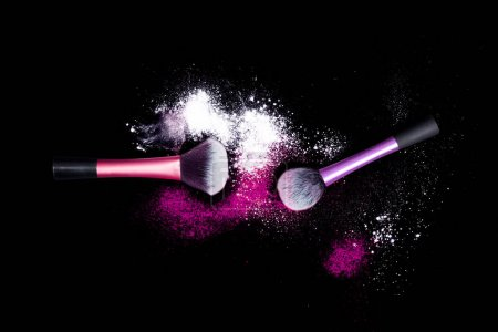 Make-up brushes with colorful powder on black background. White and pink color powder on brushes.