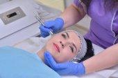 Mladá krásná žena dostane profesionální omlazení pleti obličeje ošetření profesionální kosmetické klinice