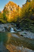 Autumn waterfall and creek woods with yellow trees foliage and rocks in forest mountain