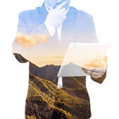 Double exposure of success businessman using tablet with green nature landscape background, concept Green IT