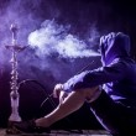 A man smokes a hookah on a black background, holid...