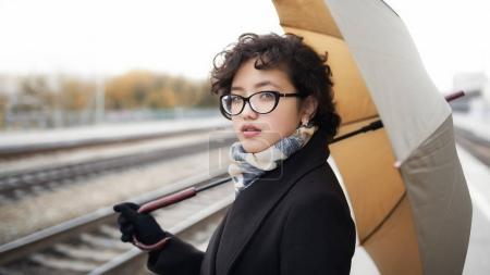 Girl in glasses standing under umbrella