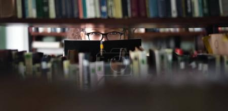 Cropped view of teenager girl looking through bookshelves