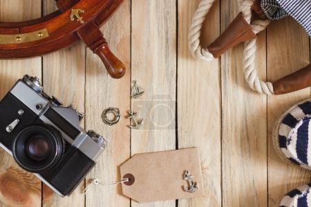 Photo pour Pantoufles rayées, appareil photo, sac et décorations maritimes sur le fond en bois, vue sur le dessus - image libre de droit