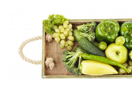 Photo for Set of different green fresh raw vegetables and fruits in the wooden tray, isolated on white - Royalty Free Image