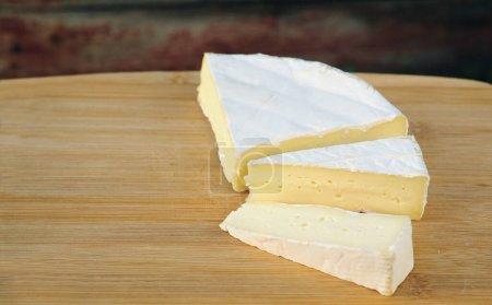 Photo pour Le fromage brie à pâte molle coupé en trois tranches repose sur une planche de bois. Camembert avec une texture délicate de couleur crème claire - image libre de droit